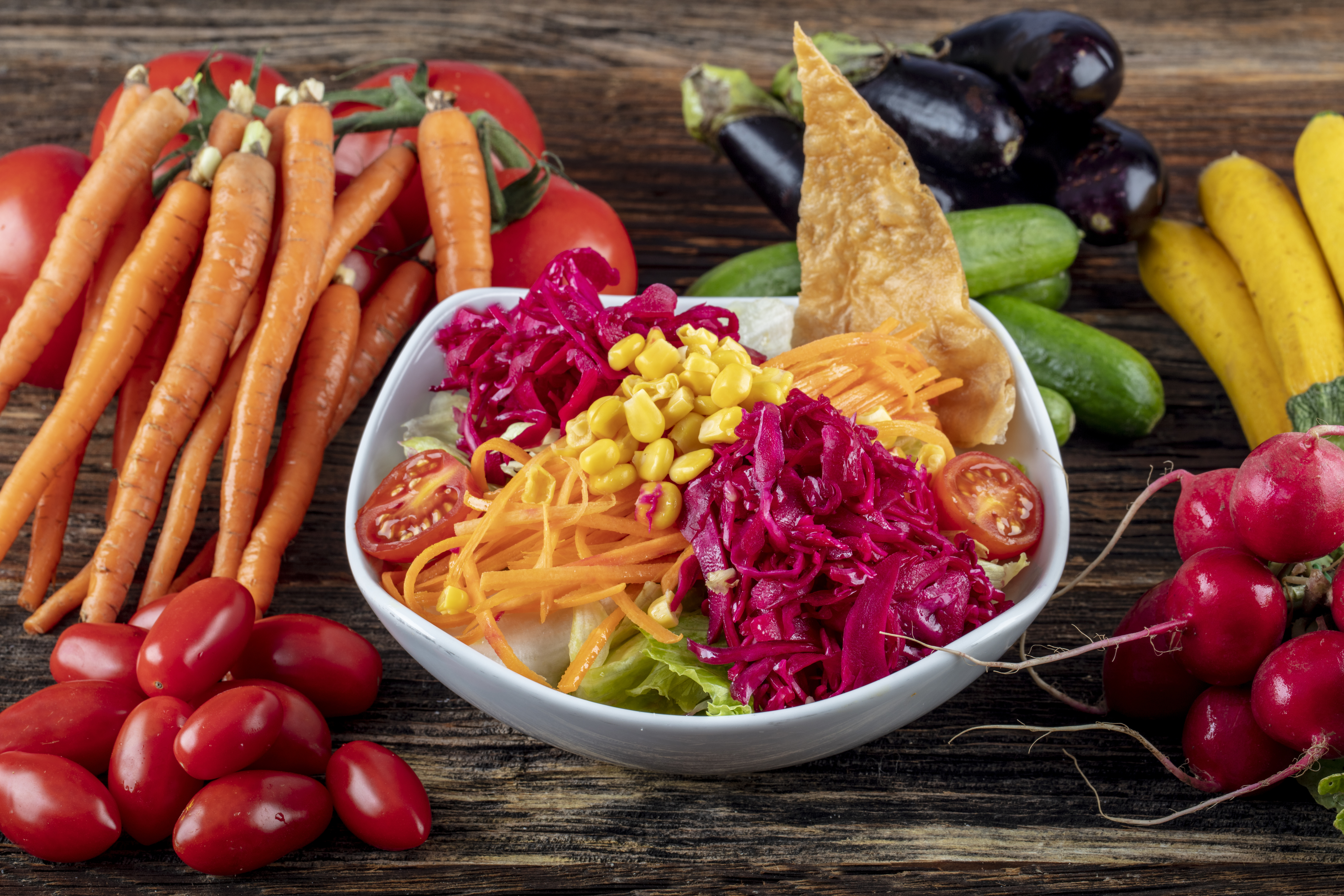 Carrot and veggies salad with lettuce, corn, red-cabbage, healthy homemade vegan food, vegetarian diet, vitamin snack.