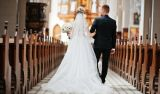 Photosession of stylish wedding couple on catholic church.