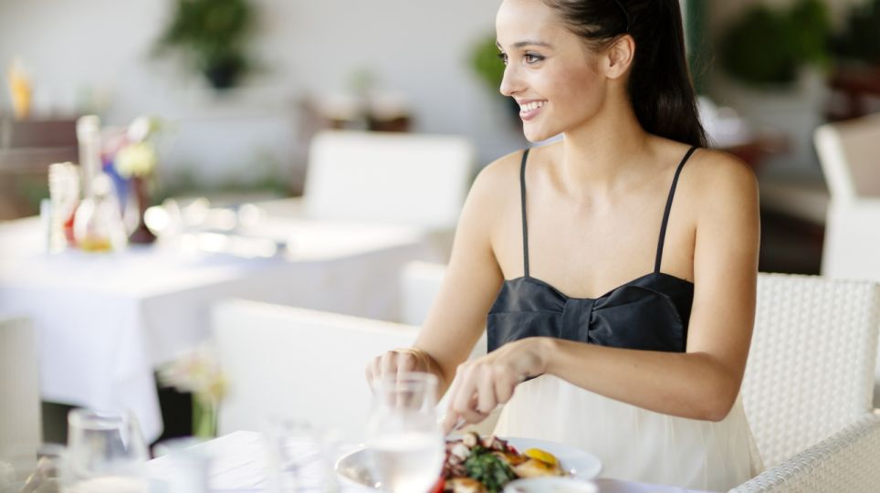 Beautiful woman eating meal in restaurant during sunset