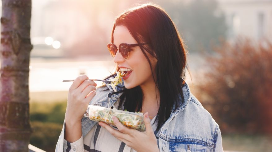 Young brunette woman in sunglasses eating fresh salad outdoor in sunset, looking away