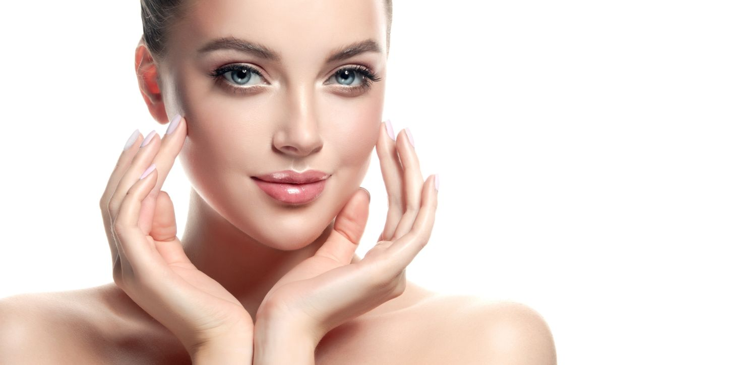 Gorgeous, young woman with clean, fresh skin is touching own face. Cosmetology.