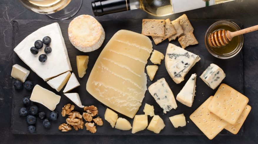 Tasting cheese dish on a dark stone plate. Food for wine and romantic date, cheese delicatessen on a black concrete background. Top view