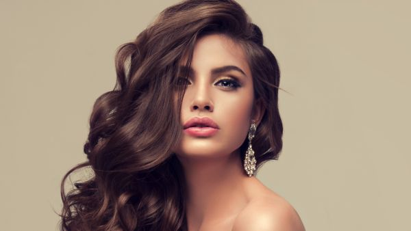 Young attractive brunette with voluminous, shiny and curly hairstyle.