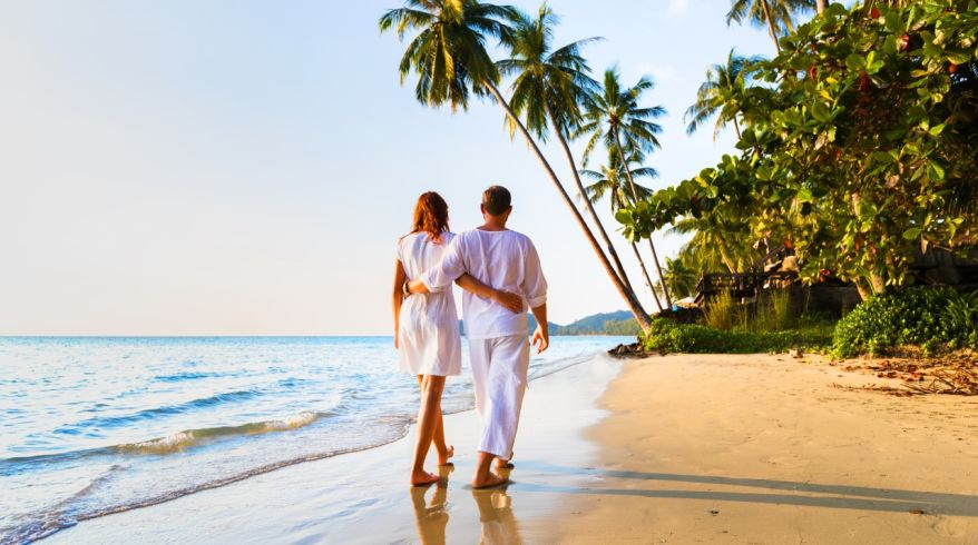 Romantic couple walking together on tropical beach, sunny summer honeymoon